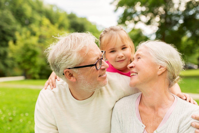 senior-grandparents-and-granddaughter-at-park-PFCPQ9W